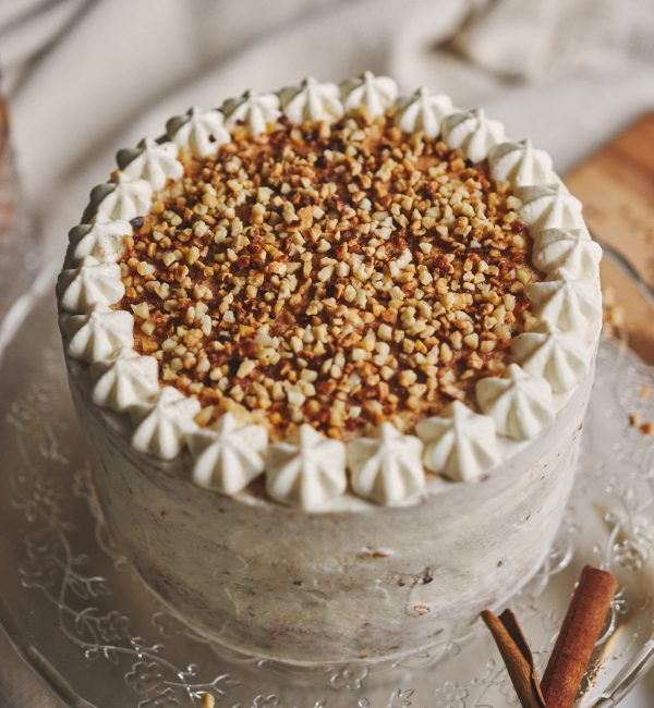 A closeup of a white delicious Christmas cake with nuts and mandarine surrounded by cinnamon  sticks - perfect background for confectionery shop